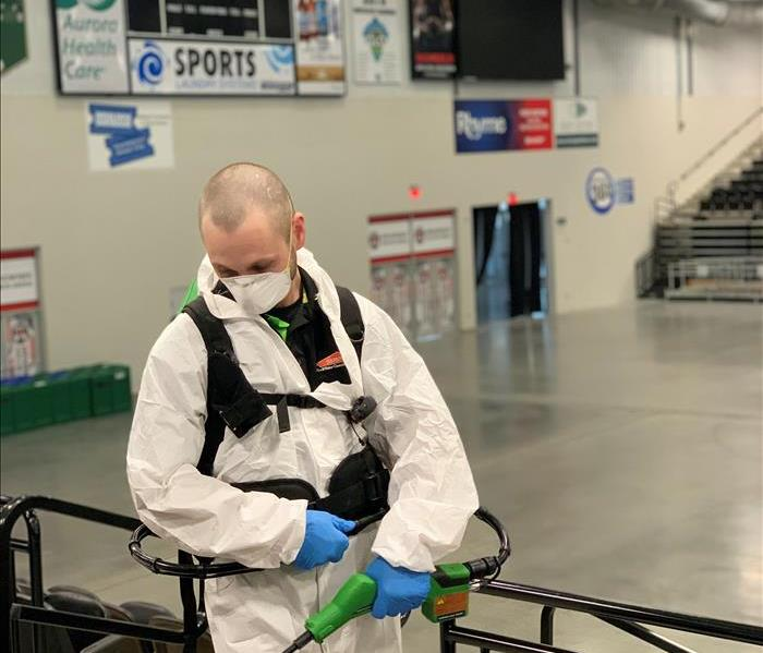 Picture of a man electrostatically spraying disinfectant